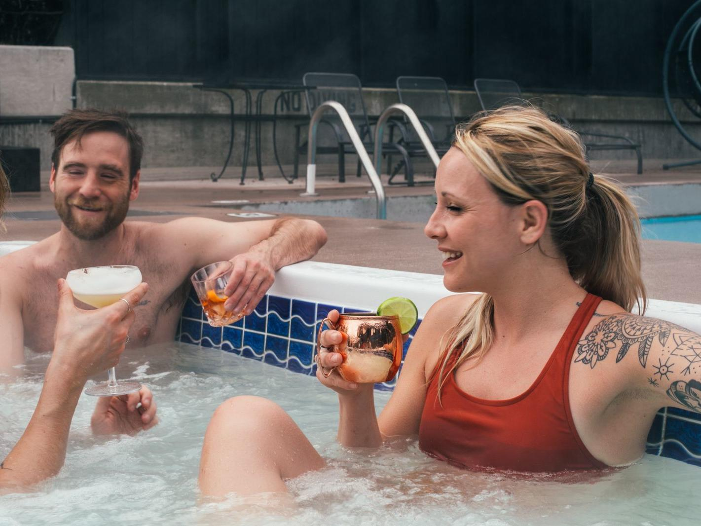 Friends in a hot tub enjoying cocktails.