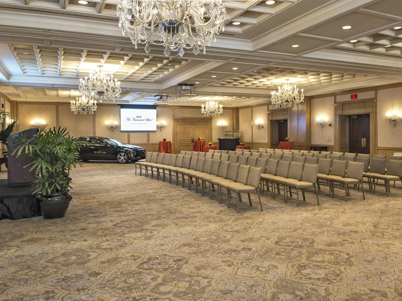 rows of chairs and a car in a ballroom