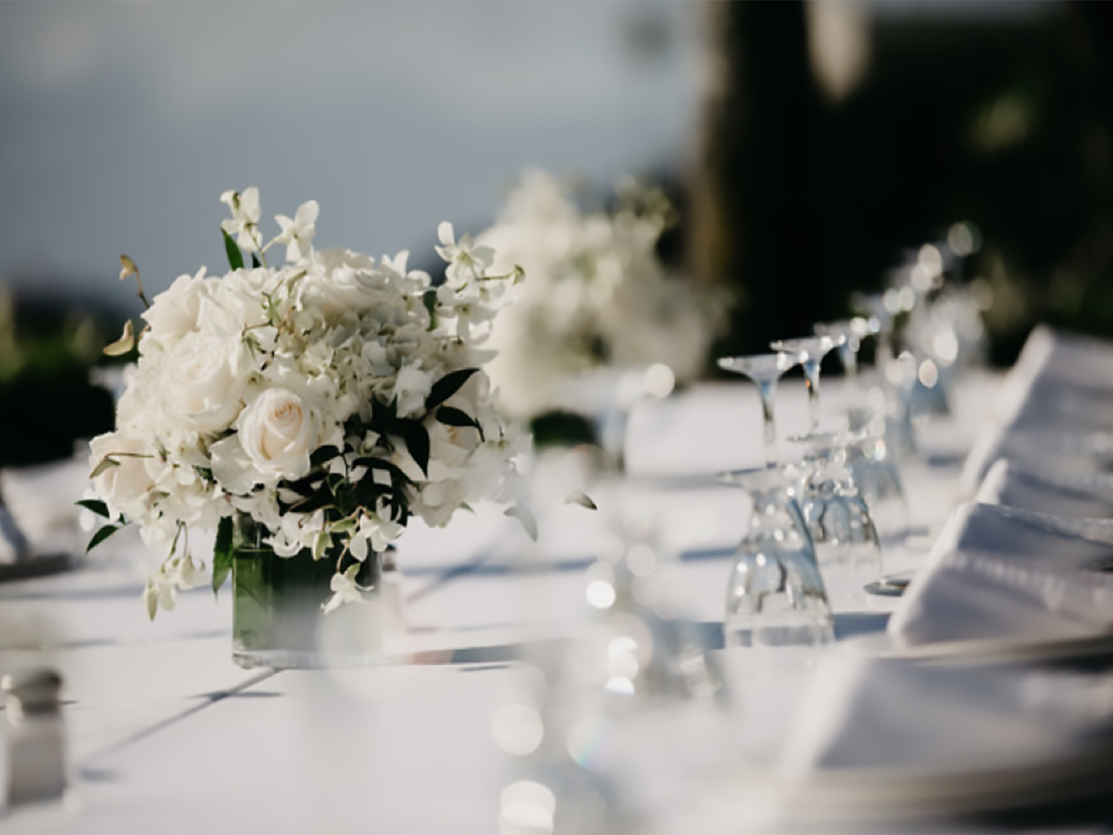 wedding table with glasses and white roses