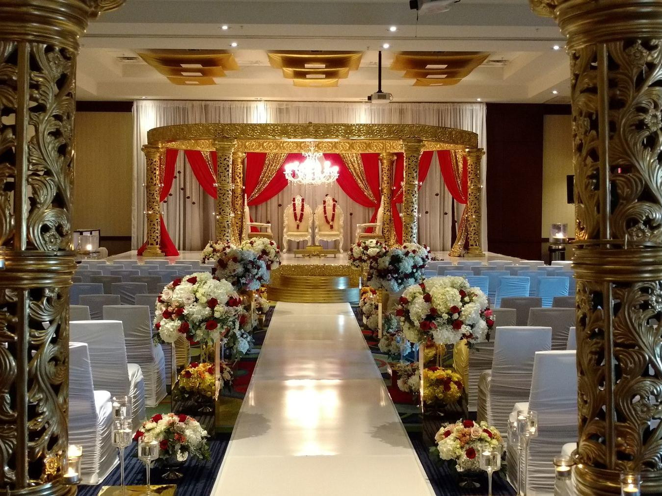 wedding aisle with flowers and chairs facing altar