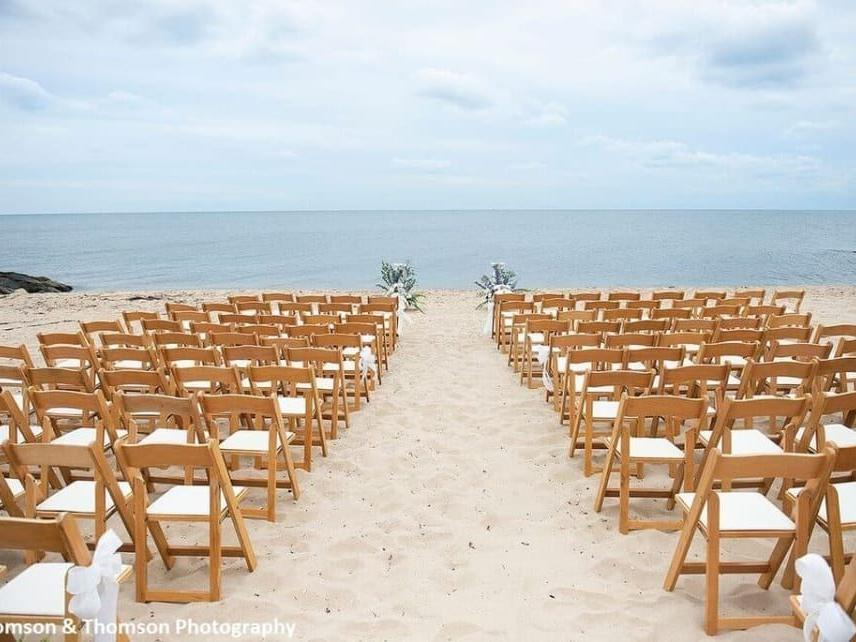 wooden chairs at beach wedding ceremony