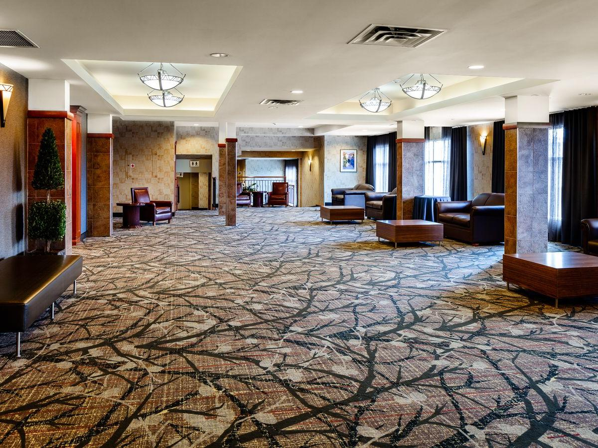 spacious, carpeted lobby area with tables and couches