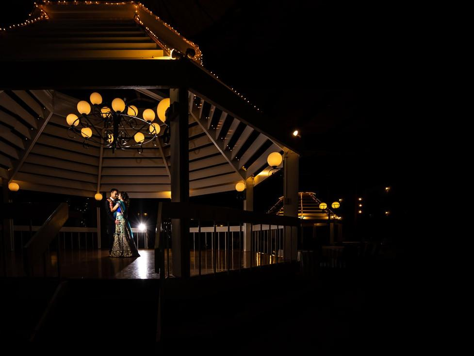 Couple dancing in gazebo at night