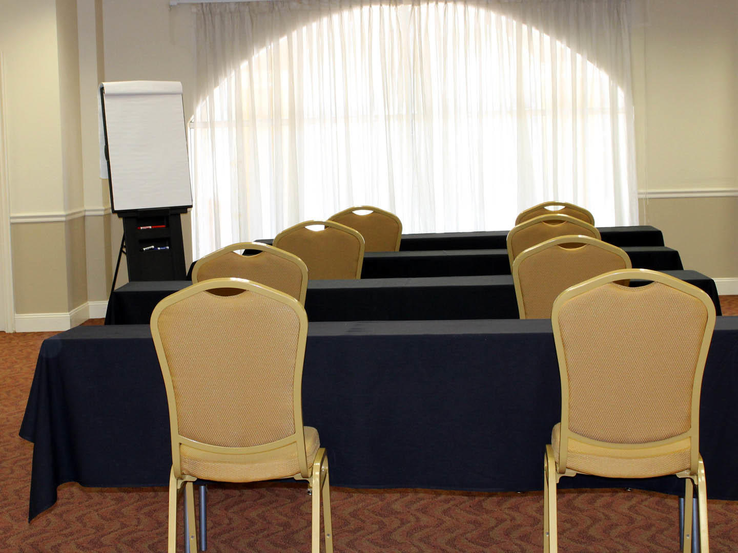 meeting room with rows of long tables and two chairs each