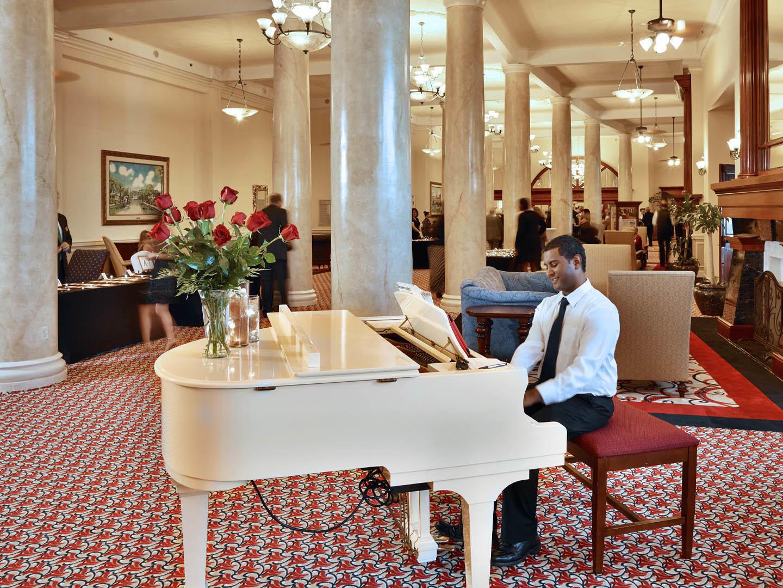 man playing white piano