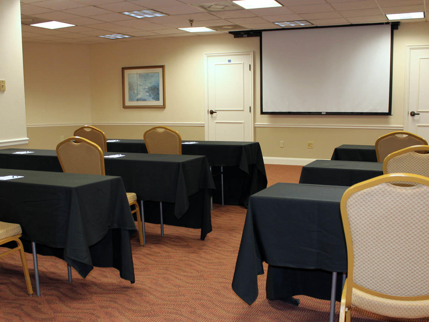 meeting room with rows of tables and two chairs at each