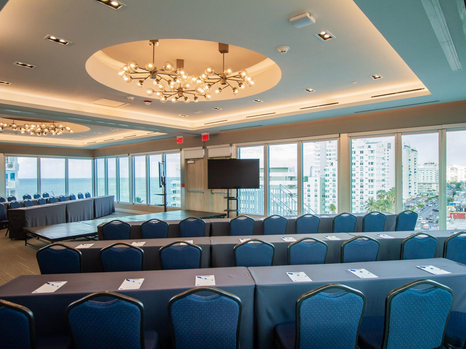 meeting room with rows of tables and chaird with television set up