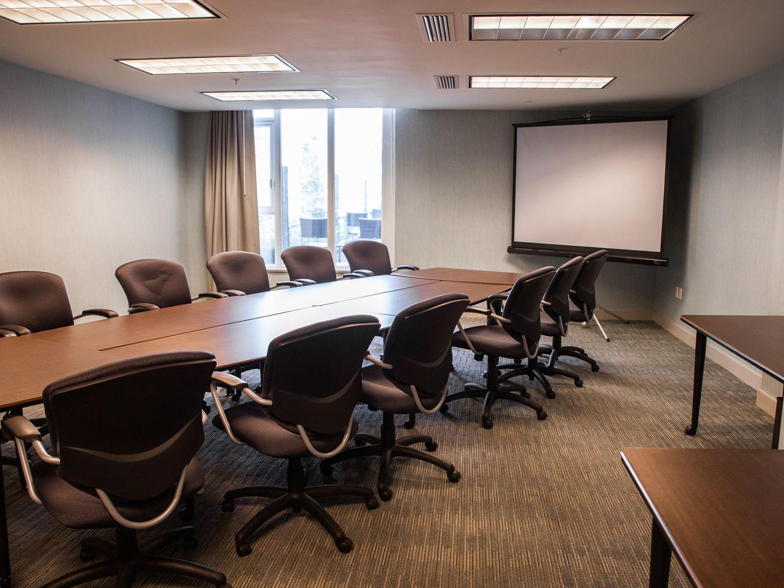 a conference table facing a projector screen