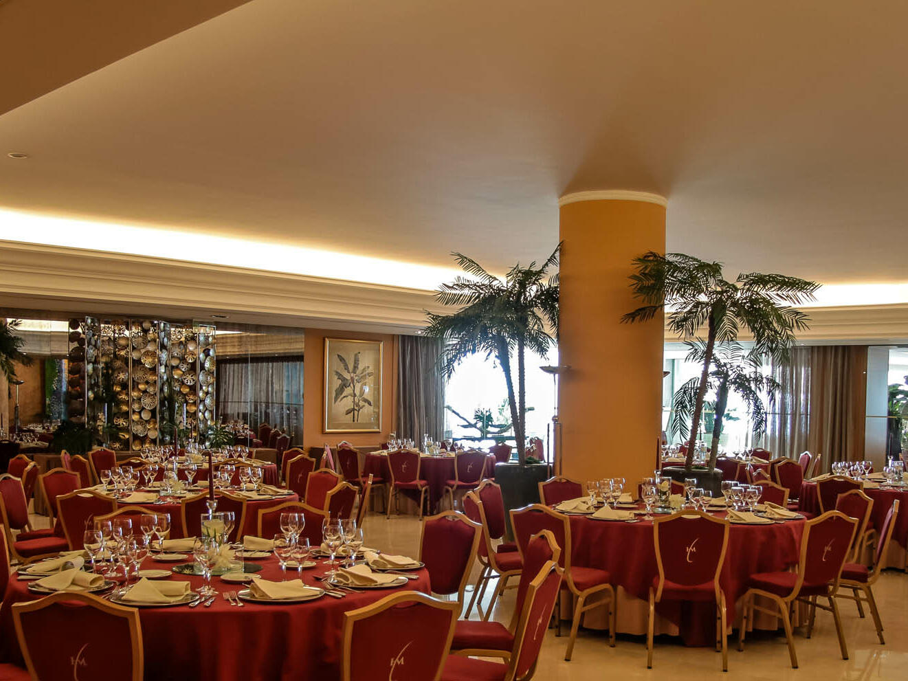 Room with round tables and red chairs at Hotel Cascais Miragem