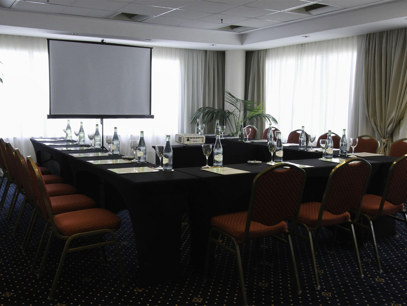 Aranjuez meeting room arranged with tables and red chairs at Hotel Emperador Buenos Aires