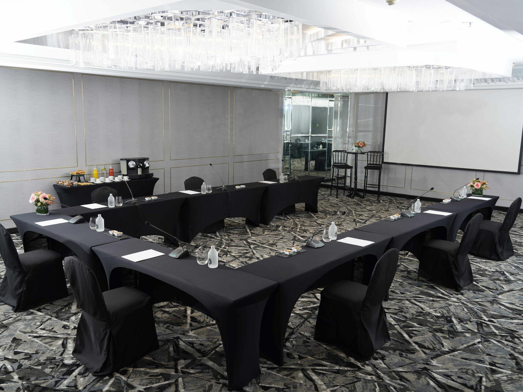 De La Castellana meeting room arranged with black tables and chairs at Hotel Emperador Buenos Aires