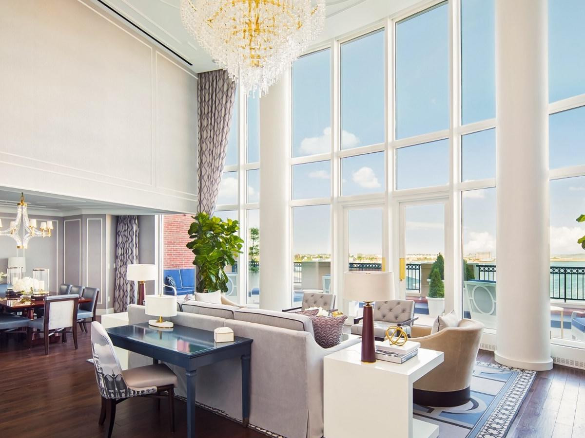 Suite living room with floor to ceiling windows and harbor views