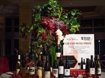 Assorted bottles of wine and large floral arrangement