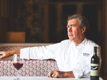 Chef sitting in booth with glass and bottle of wine