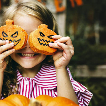 a young girl holding pumpkin cookies