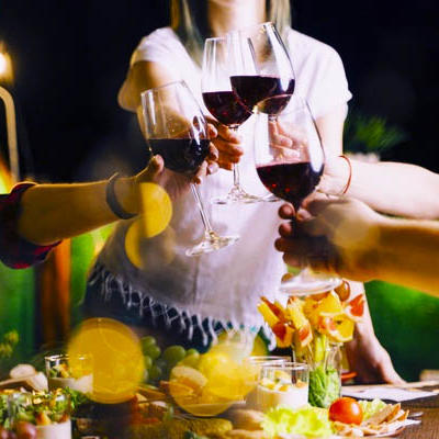 a group of people cheers wine glasses