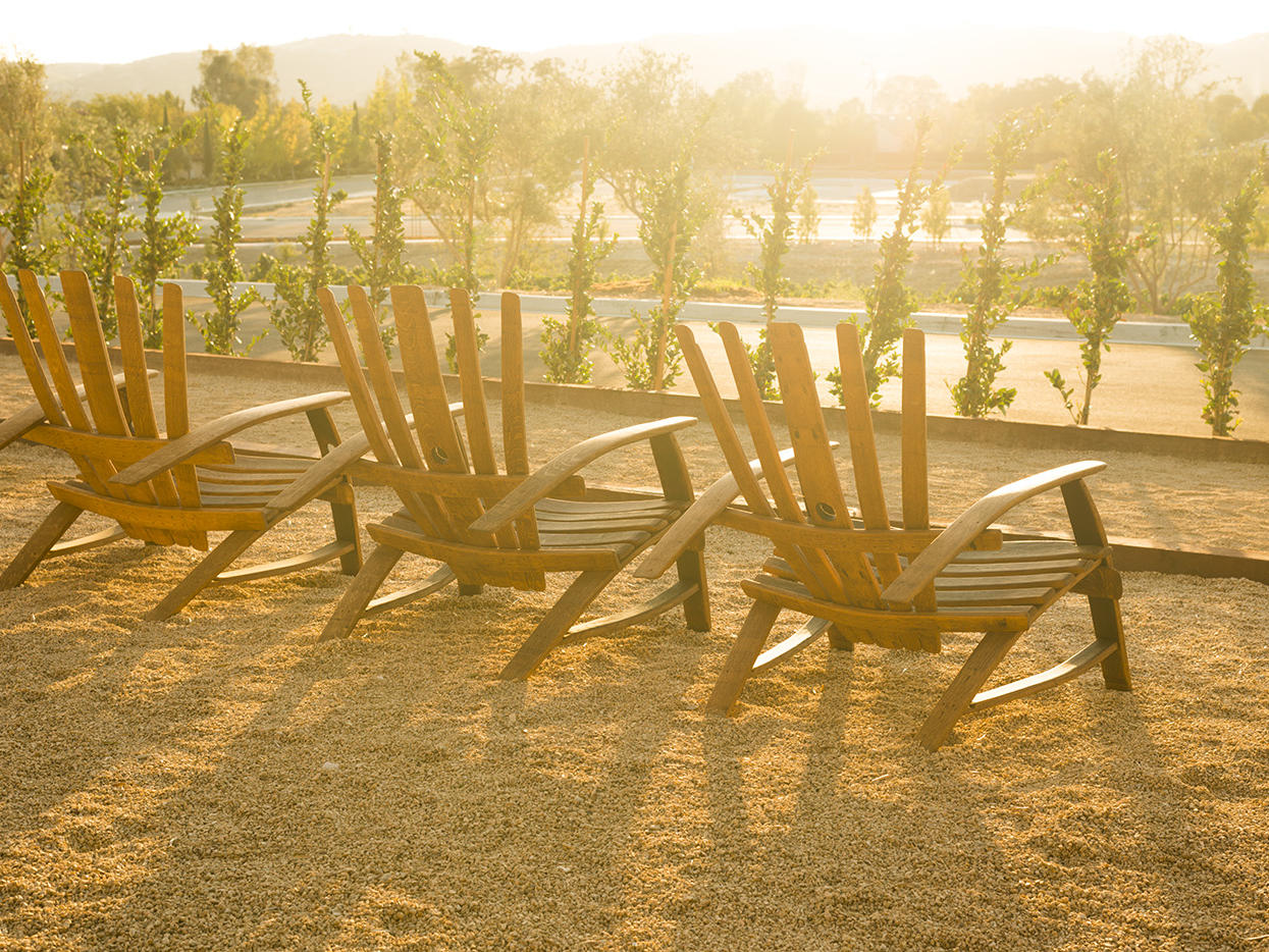 Three wooden lounge chairs facing towards sunset and vineyard