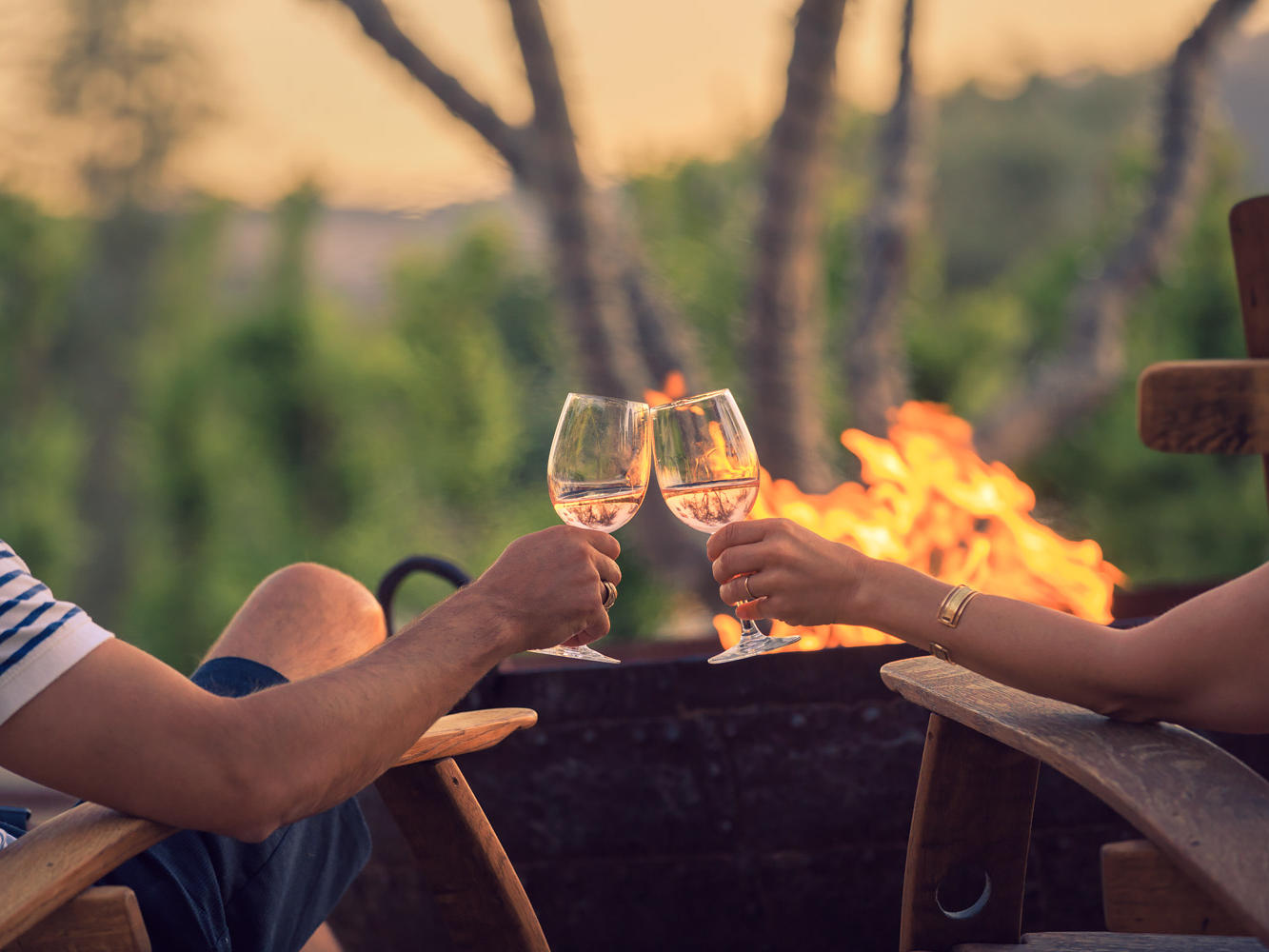 Guests sitting in front of fire pit with wine glass in hands