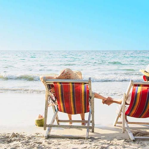 a couple holding hands in beach chairs