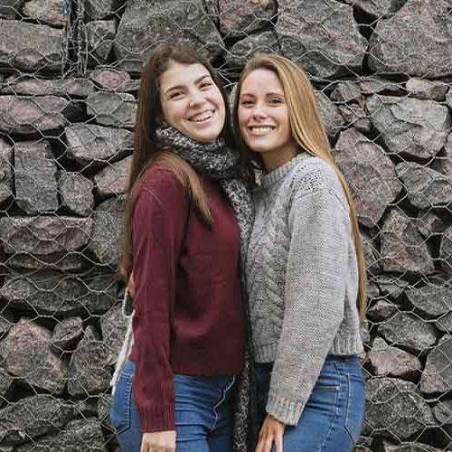 two girls wearing sweaters pose for a picture