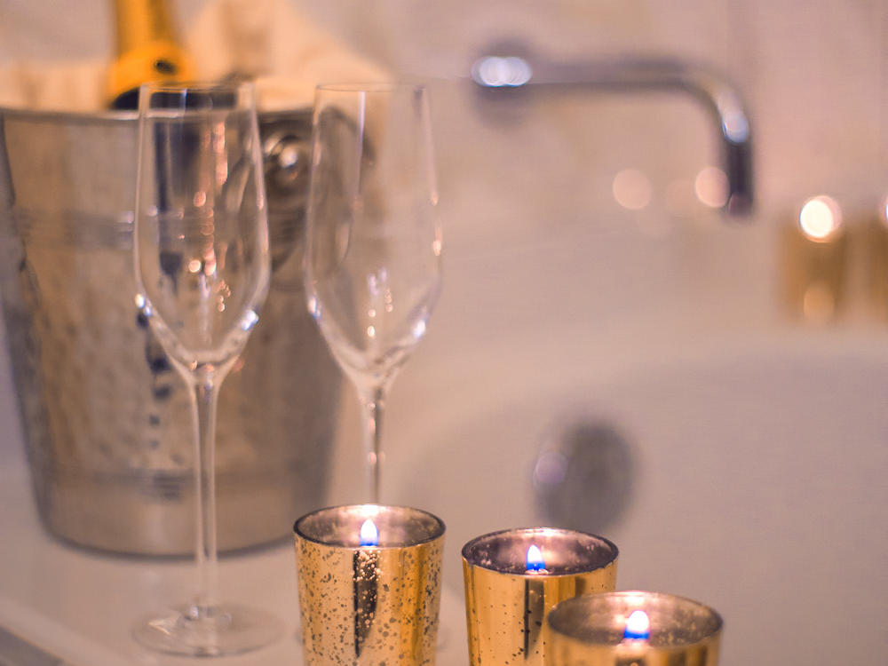 Wine bucket, bottle of wine, wine glasses and candles next to tub