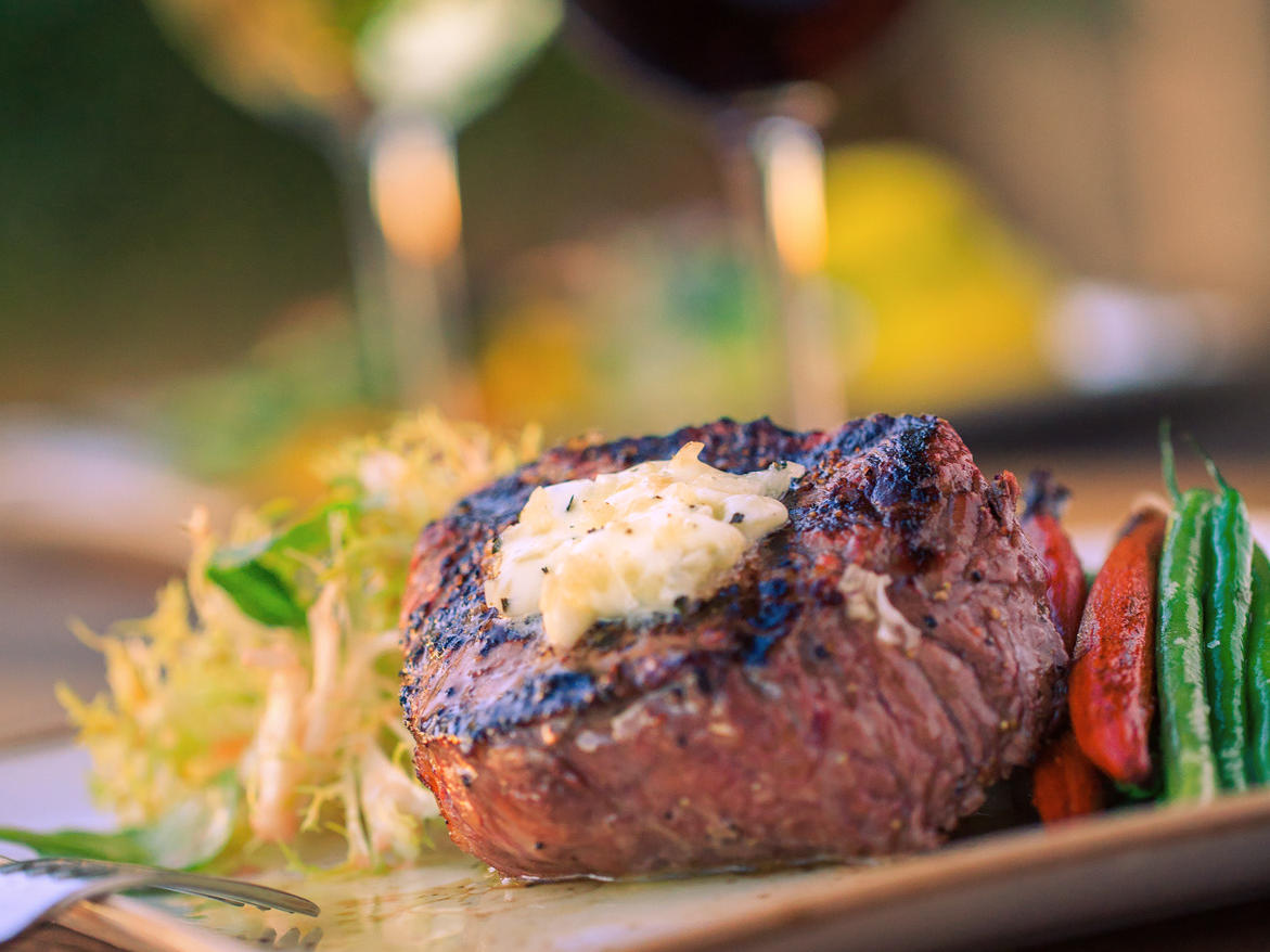 Steak filet with veggies and glass of red wine
