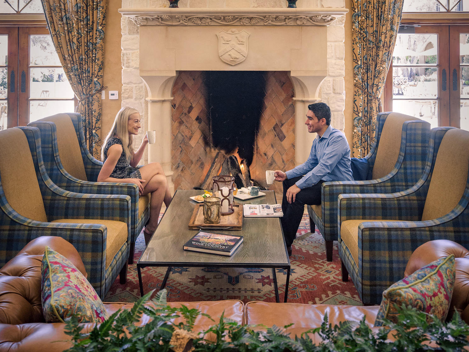 Man and woman sitting in front of fireplace drinking coffee