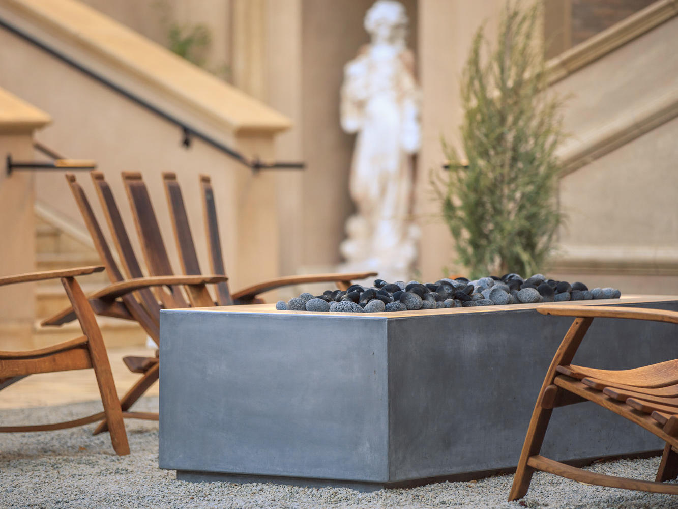 Fire pit and chairs with sculpture in the back