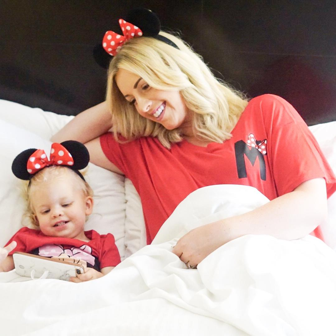 mom and daughter wearing minnie ears in bed