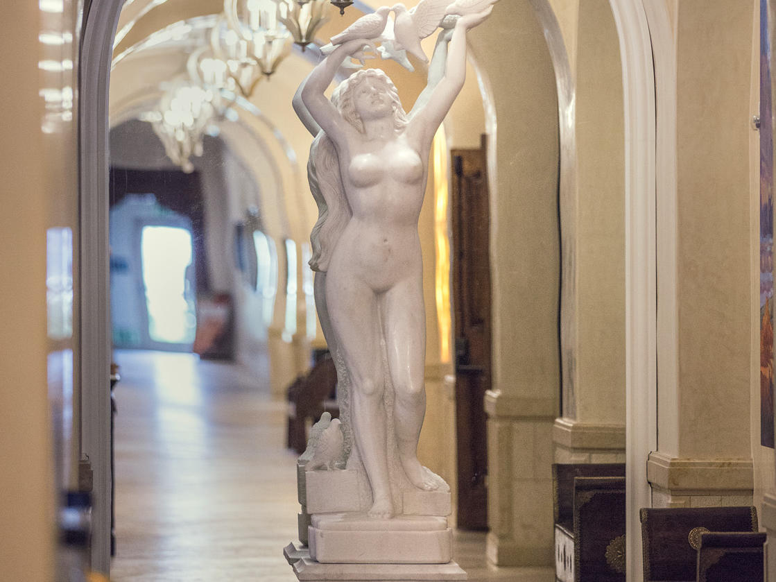Statue of woman with birds at end of hallway