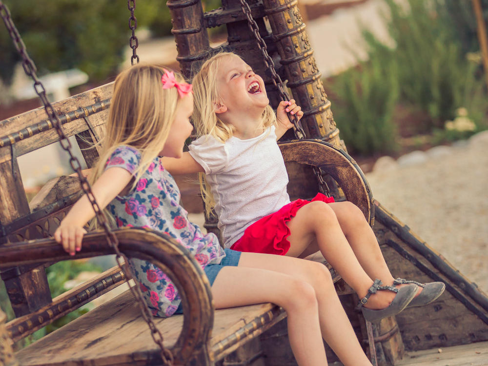 Two children sitting on a swing in courtyard