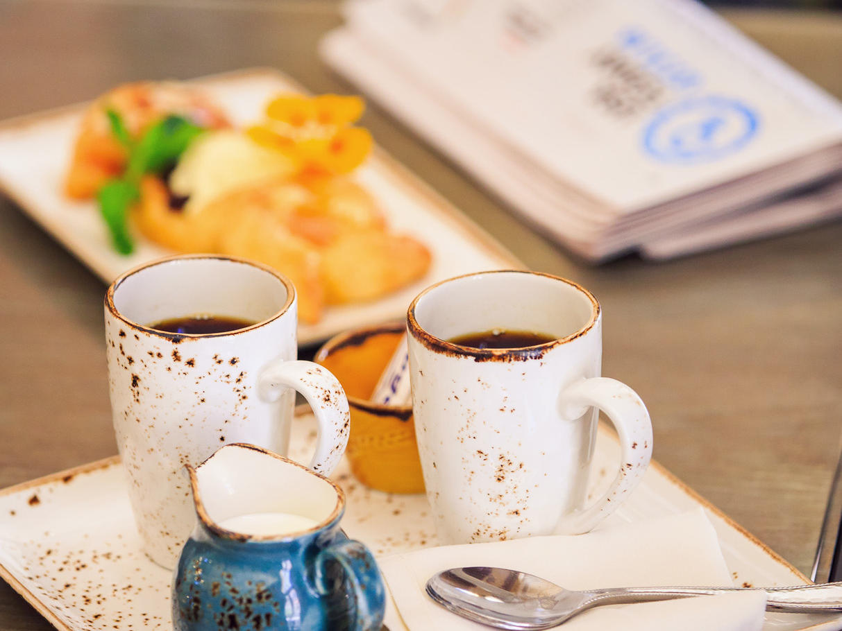 Two coffee cups, creamer, breakfast plate, and newspaper on table