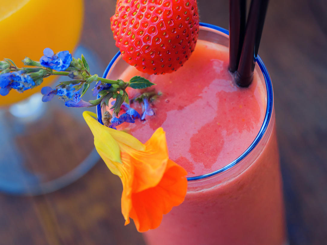 Strawberry smoothie adorned with purple and orange flowers