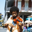 A man playing a violin in the streets near the hotel