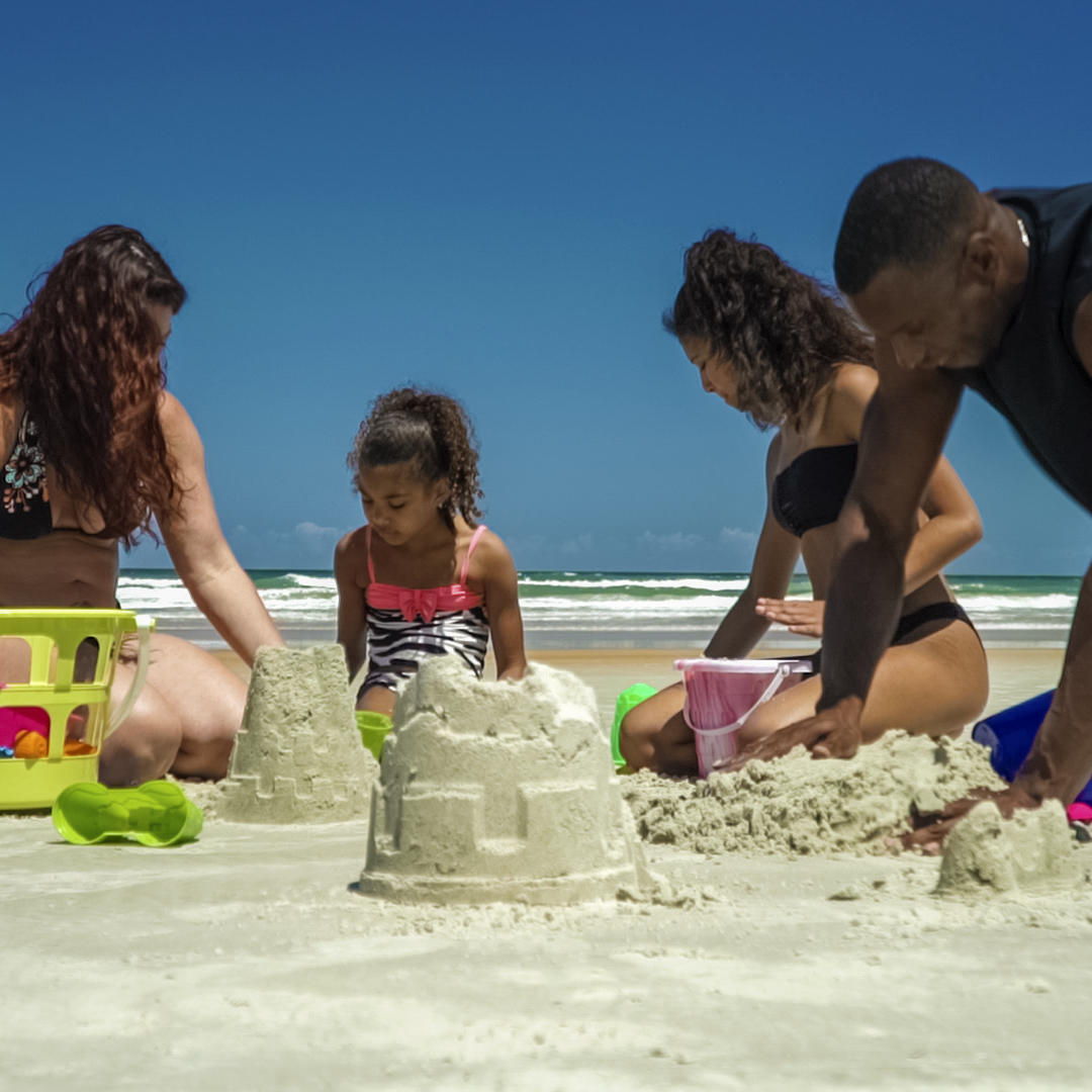 family building sand castle on beach