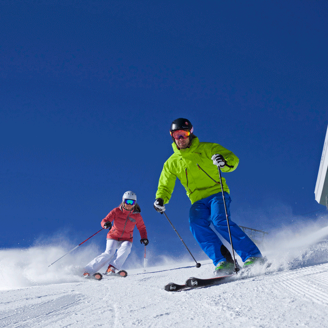 two people skiing down a hill