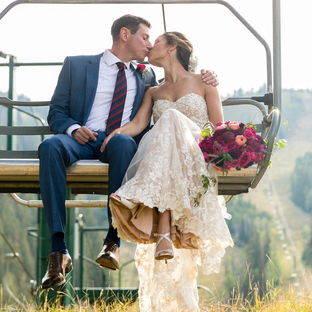 a bride and groom on a ski lift