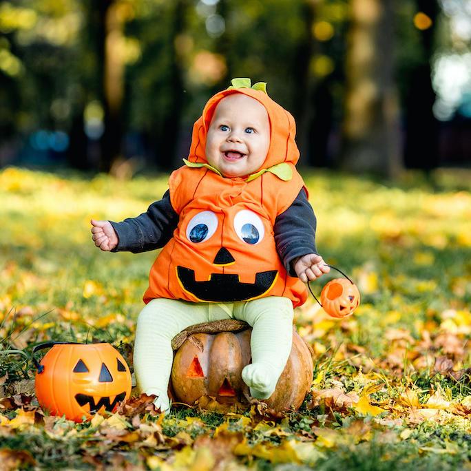 a baby dressed up like a pumpkin