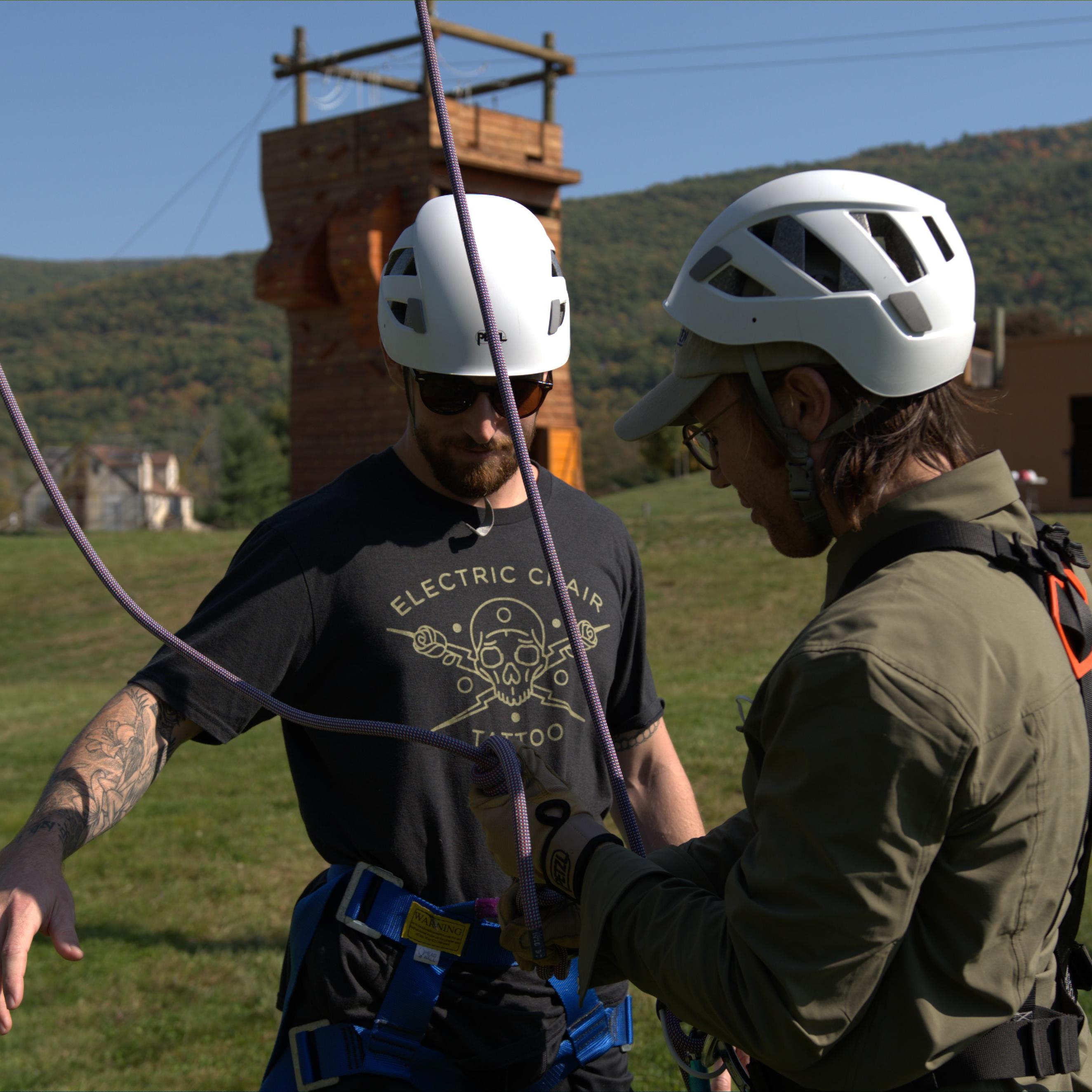 Man getting strapped into ropes course