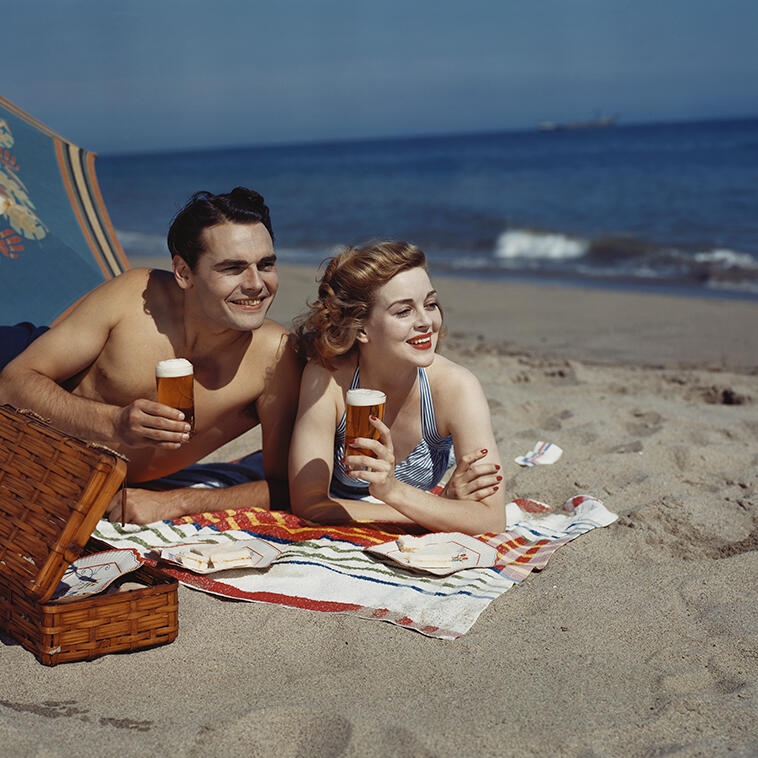 A couple laying on beach and having snacks at  Inn Hotel Ocean