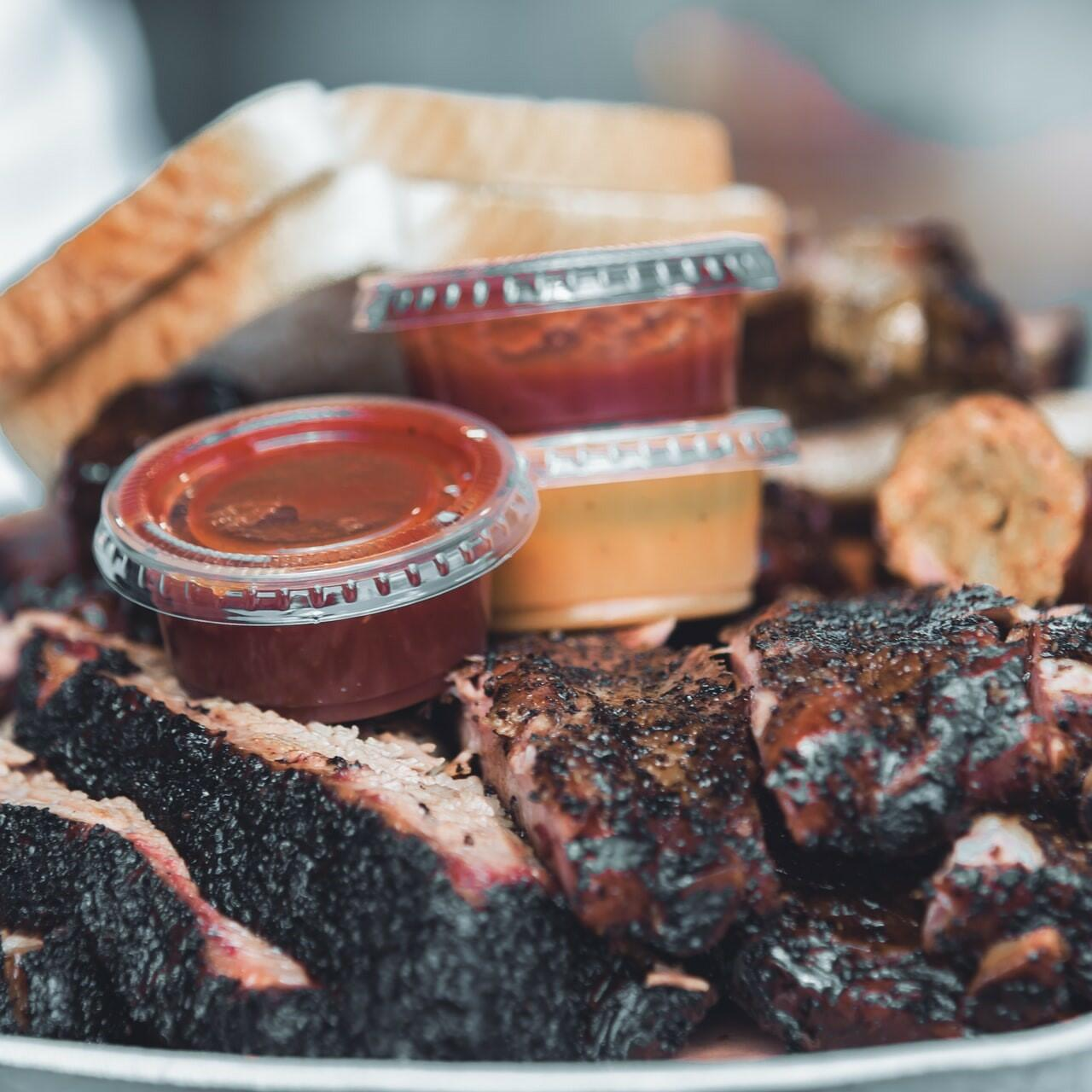A closeup picture of barbeque meat with sauces and bread