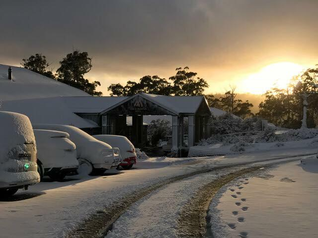 Hotel and vehicles covered with snow at Cradle Mountain Hotel