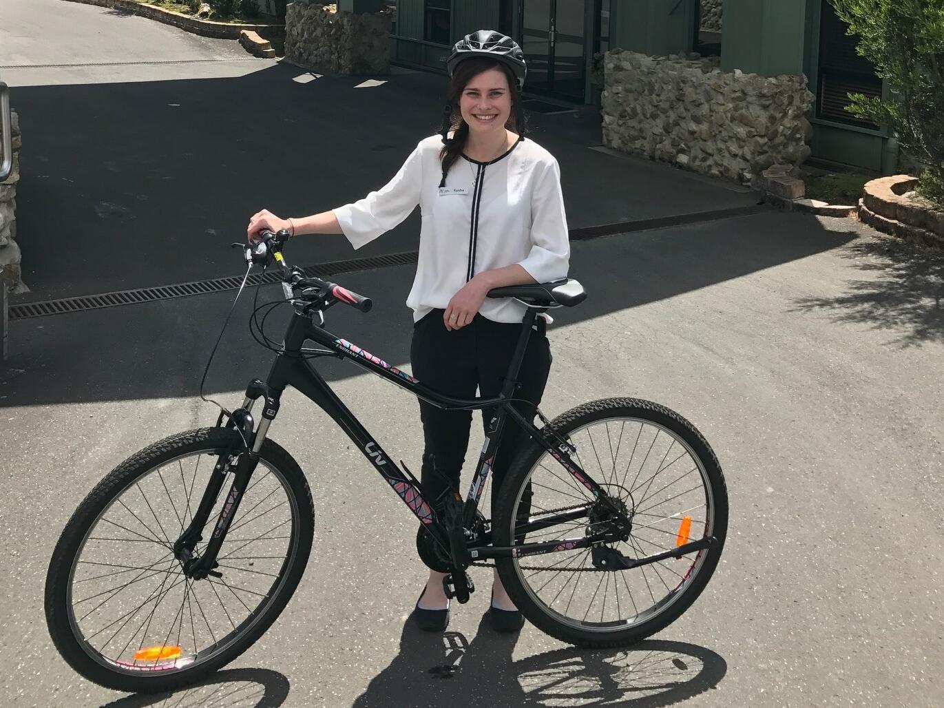 A lady holding a bike near Cradle Mountain Hotel