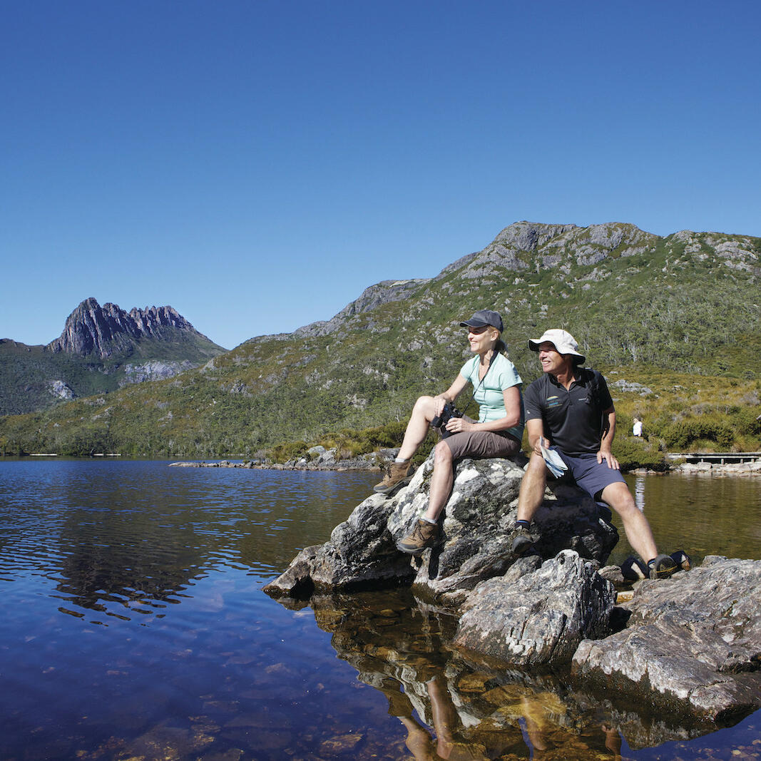 2 men sitting on a rock at dove lake near Cradle Mountain Hotel