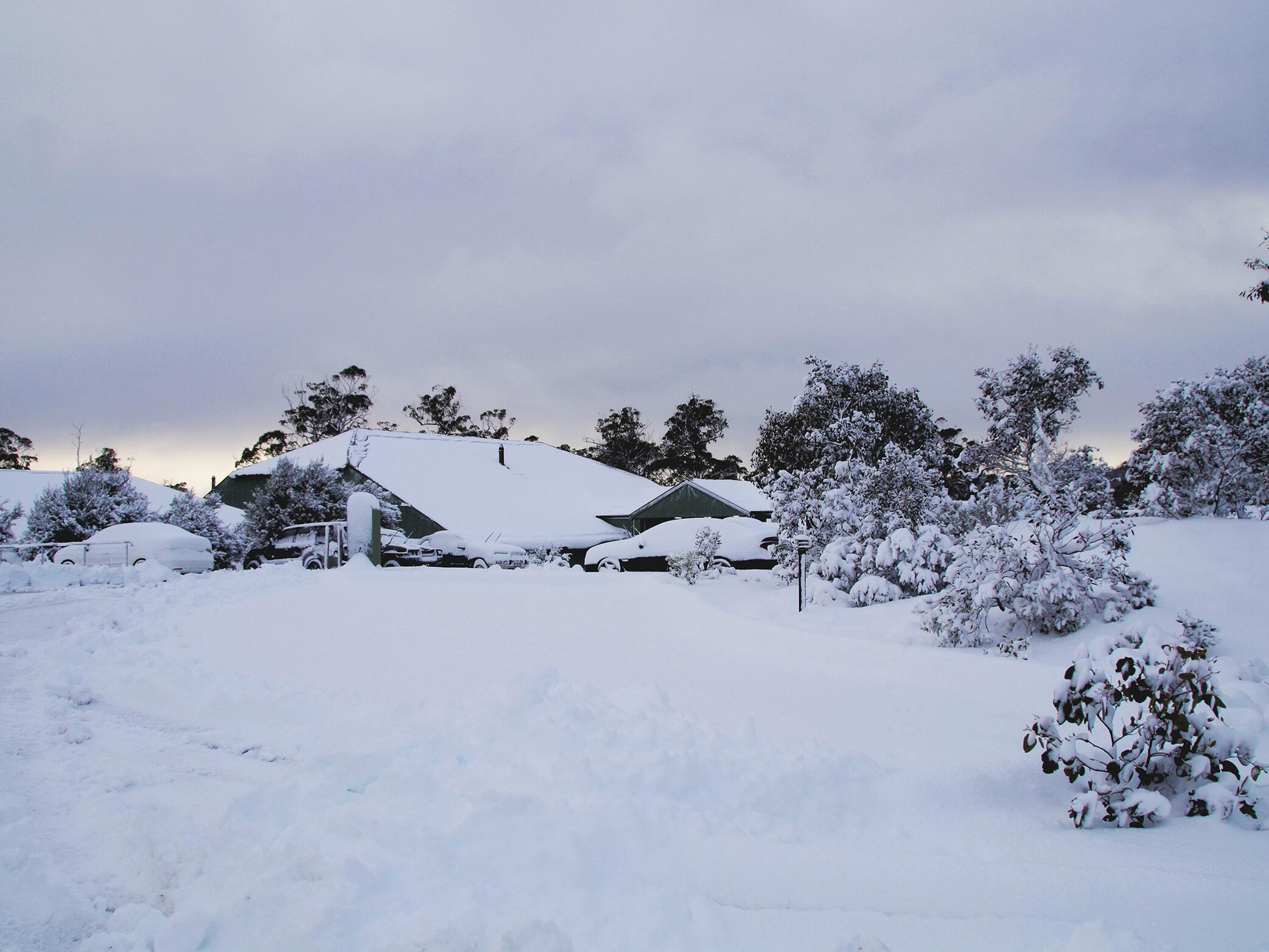 Exterior view of Cradle Mountain Hotel covered with snow