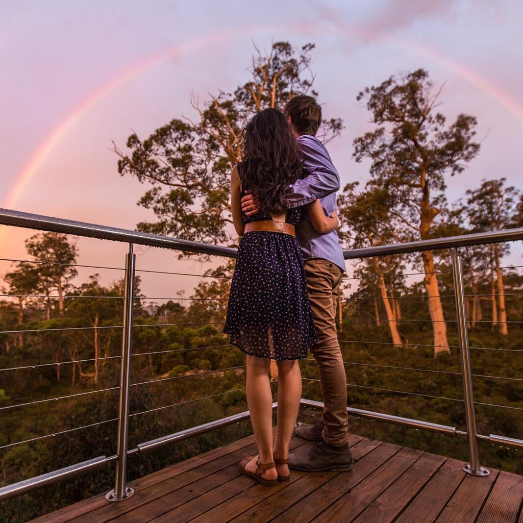 Couple looking at rainbow from Cradle Mountain Hotel