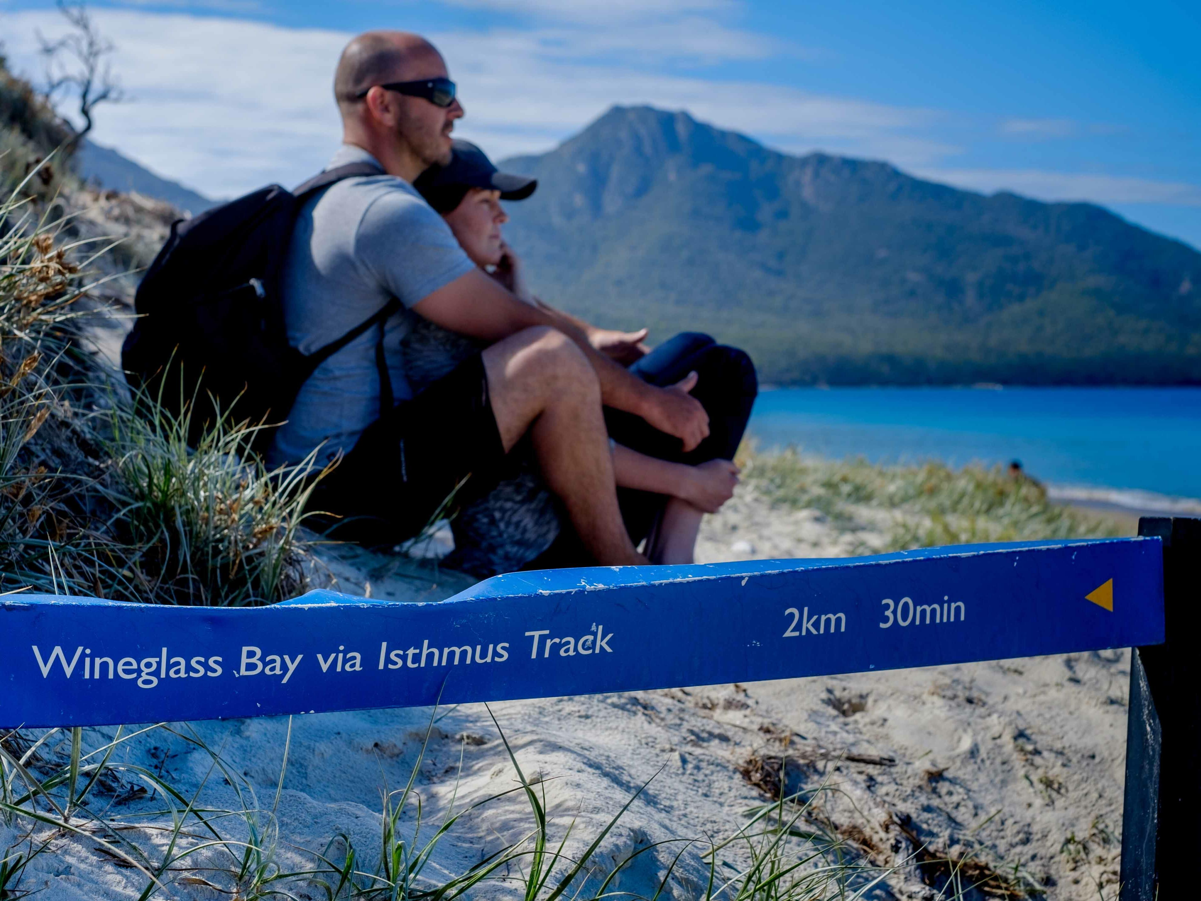 Couple sitting at the beach at the Bay in Freycinet Lodge