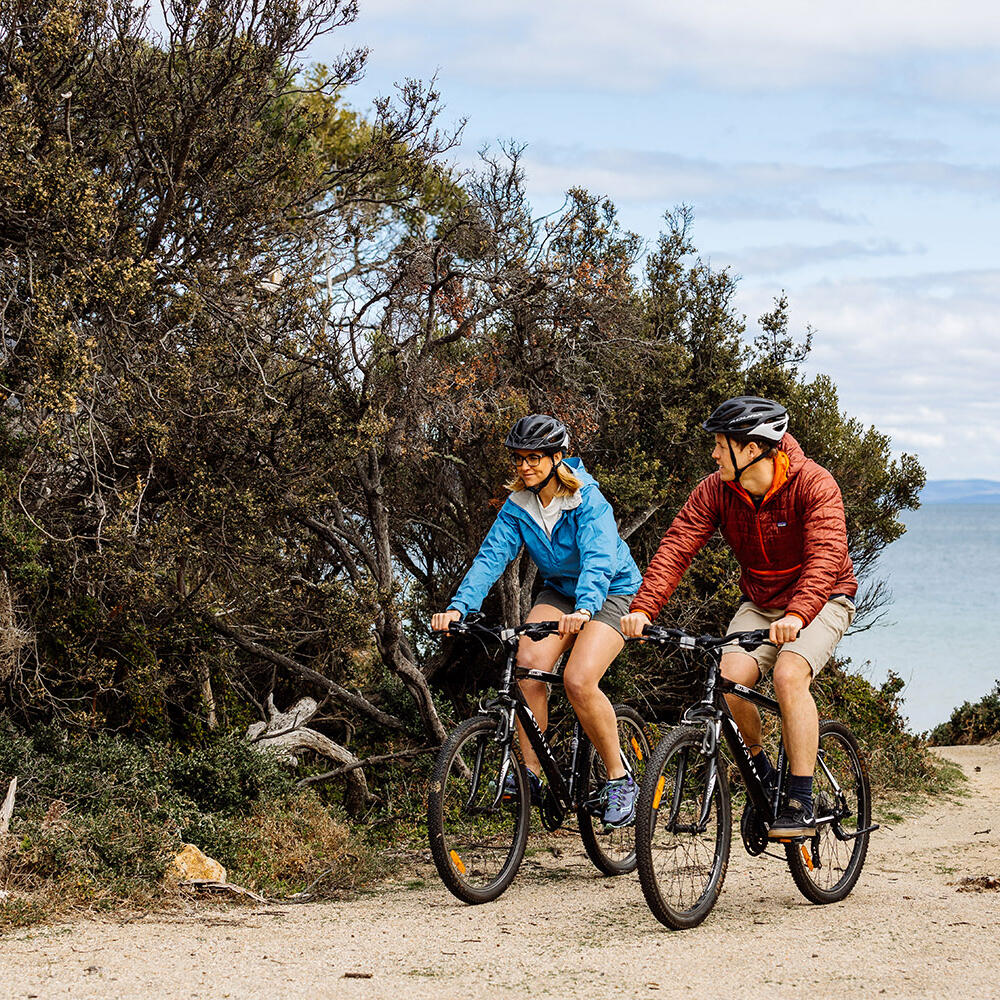 Couple riding bikes on a trail at Freycinet Lodge