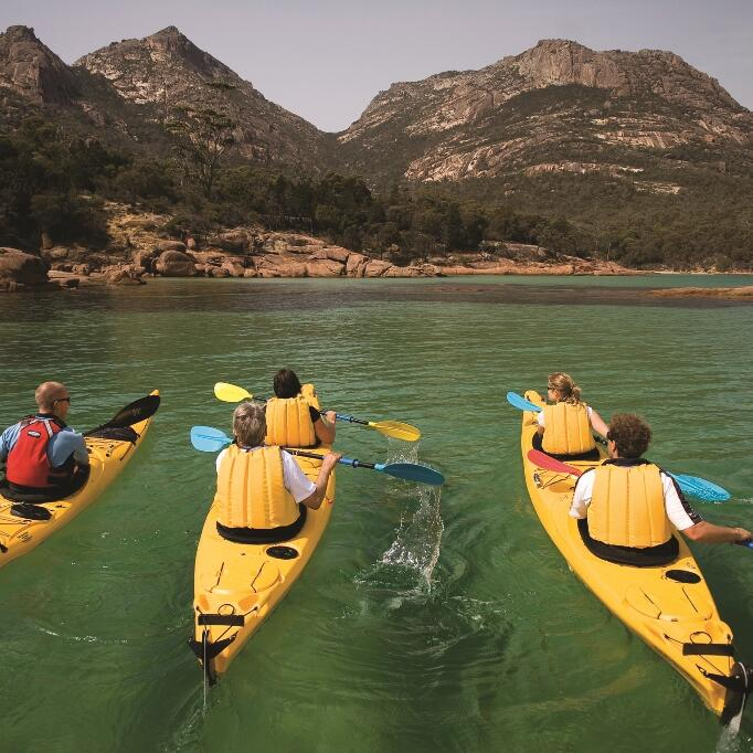 people on kayaking at the bay near Freycinet Lodge