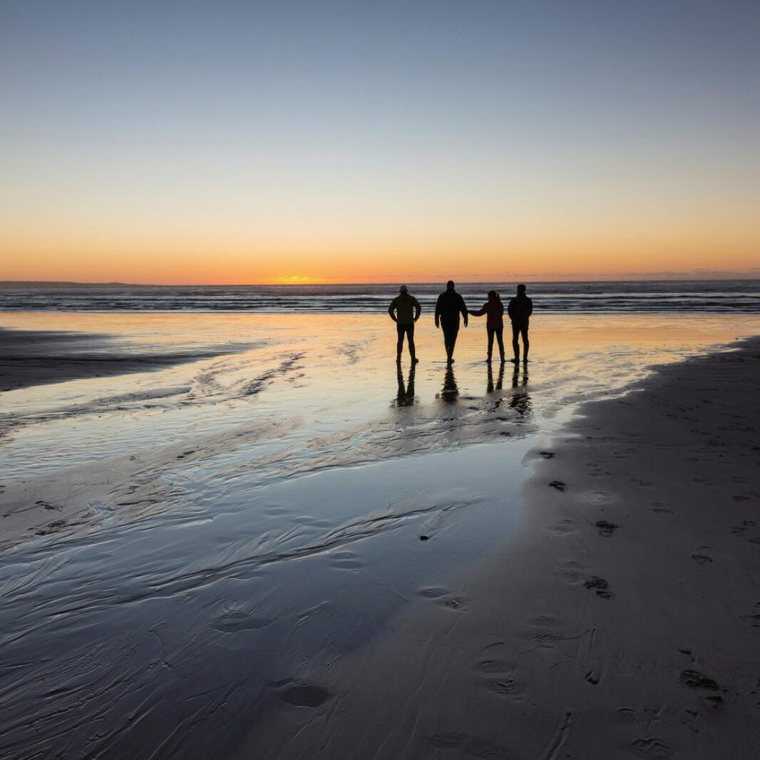 People walking on the sunset at the beach near Strahan Village